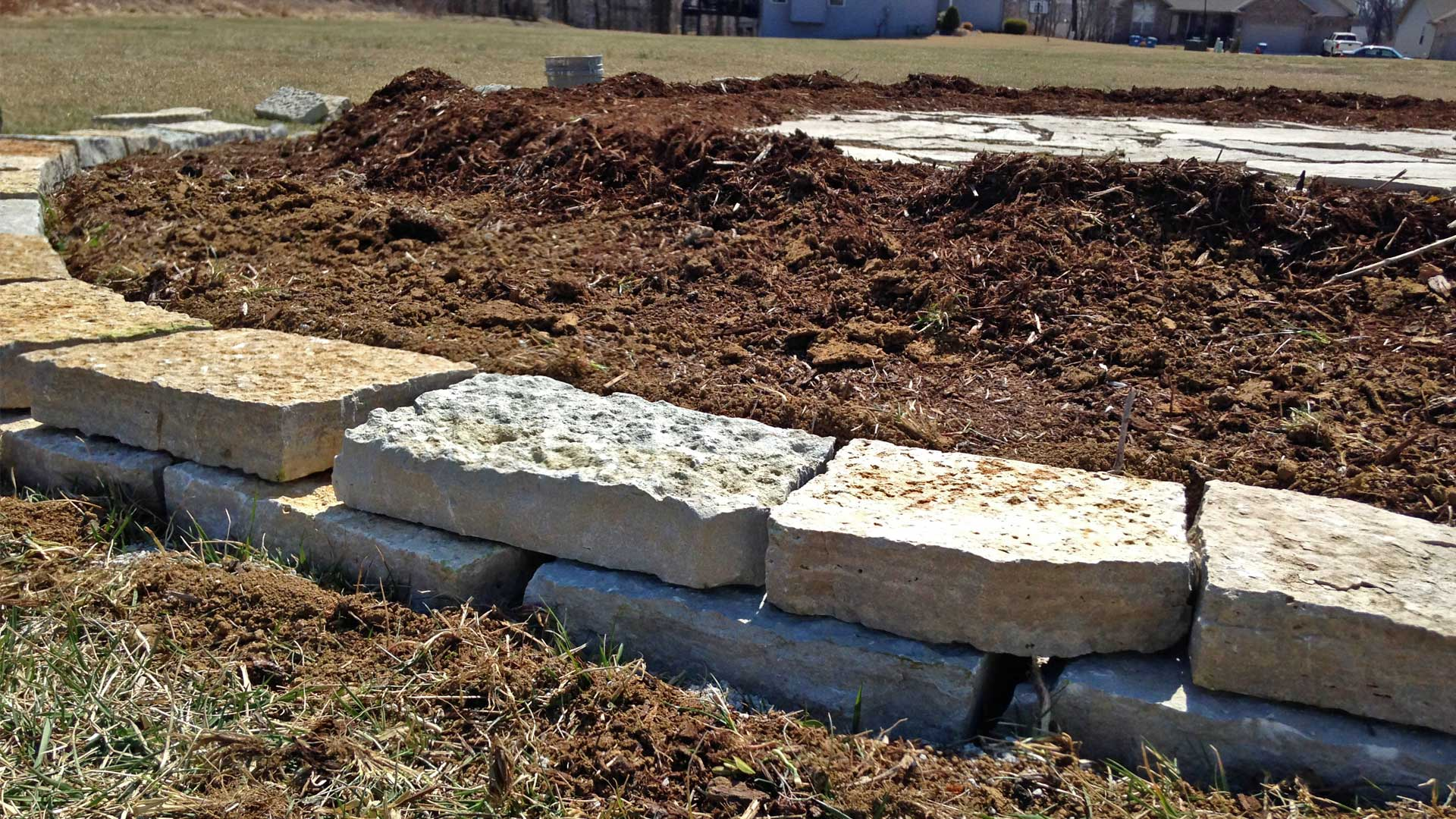 Rock edging around a landscaping bed after leveling land in Alton, IL.