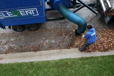 Element Turf & Outdoor Solutions, LLC leaf removal truck picking up leaves on a curb in Godfrey